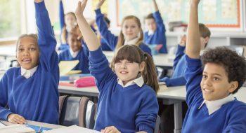 Elementary school children wearing blue school uniforms raising hands in classroom